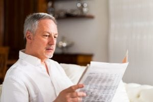 57754594 - portrait of a mature man reading a newspaper